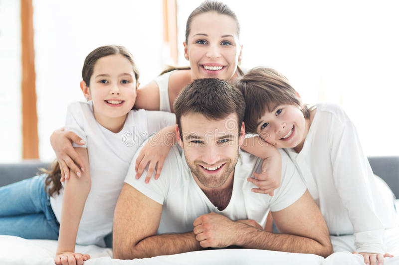 Smiling family in bed. Smiling family lying together on bed