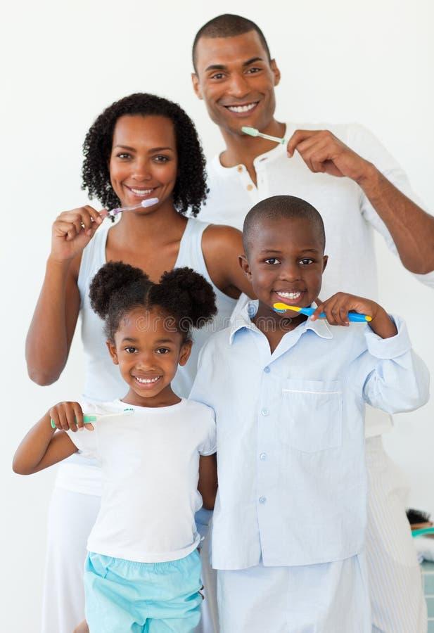 Smiling family brushing their teeth royalty free stock image