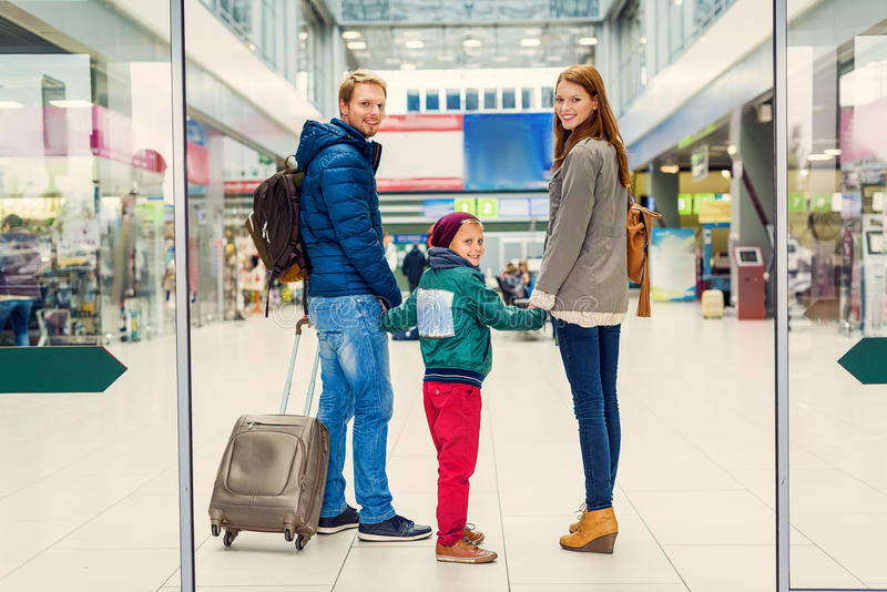 Smiling family with child at airport stock photography