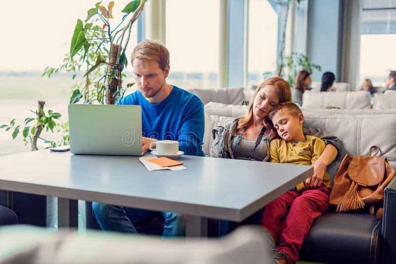 Smiling family with child at airport. Relaxation time. Young father enjoying laptop while mother and son sleeping on couch in airport lounge stock photo