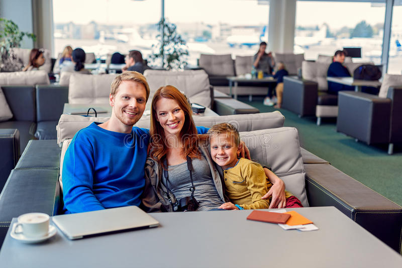 Smiling family with child at airport. Almost time for takeoff. Loving father, mother and their son hugging at airport, going on holiday while in waiting area stock images
