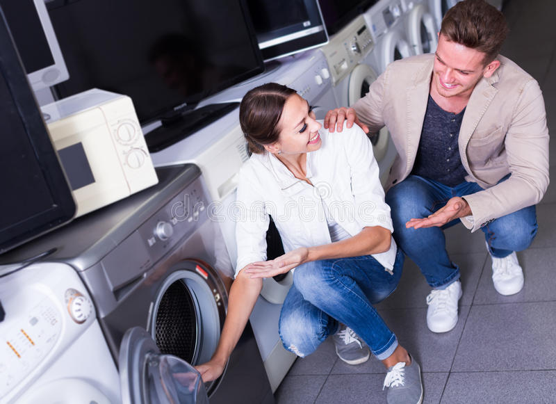 Smiling family couple buying new clothes washer royalty free stock photo