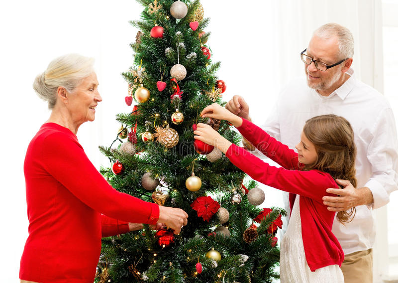 Smiling family decorating christmas tree at home. Family, holidays, generation and people concept - smiling family decorating christmas tree at home royalty free stock photography