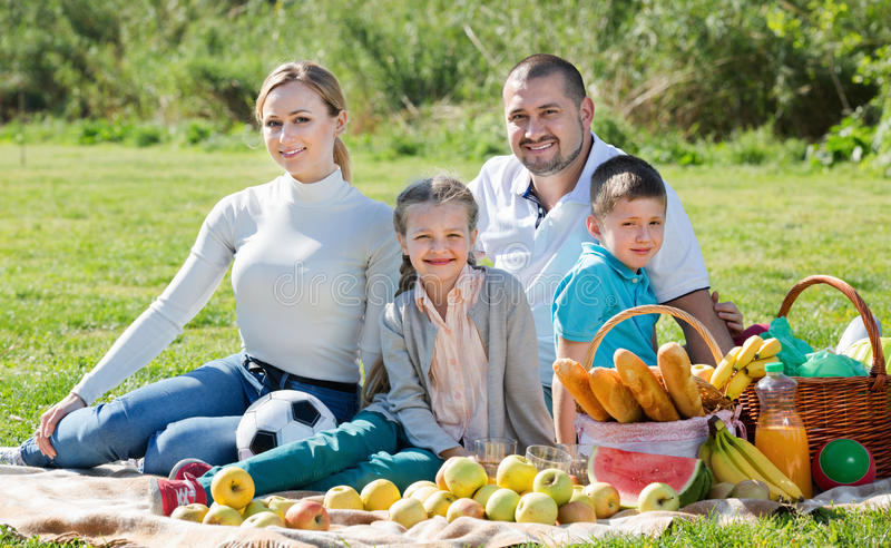 Smiling family of four having a picnic outdoors. In a sunny weather royalty free stock photo