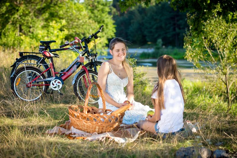 Happy smiling family having picnic near river after riding bicycles stock images