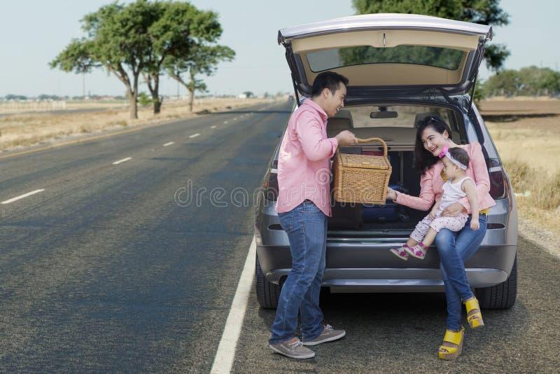 Smiling family holding picnic basket stock photography