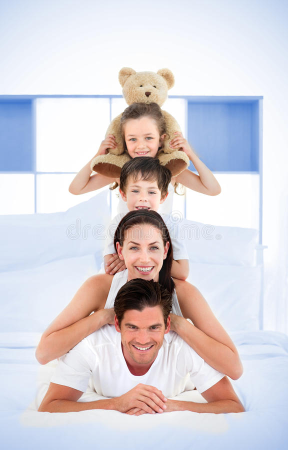 Smiling family leaning on each others shoulders in bed royalty free stock photo