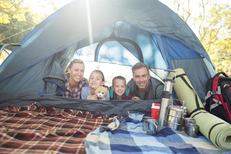 Smiling family lying in the tent stock images