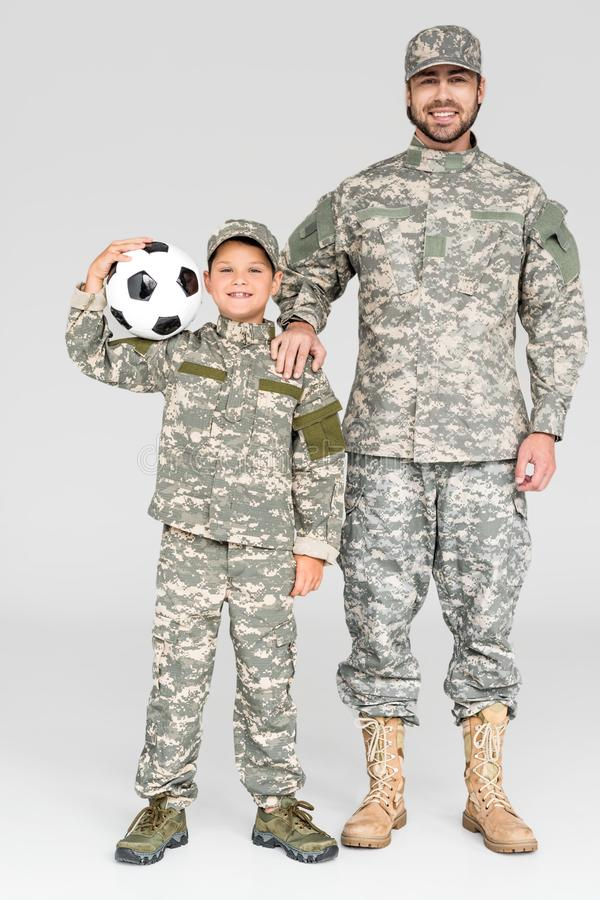 smiling family in military uniforms with soccer ball looking at camera royalty free stock photos