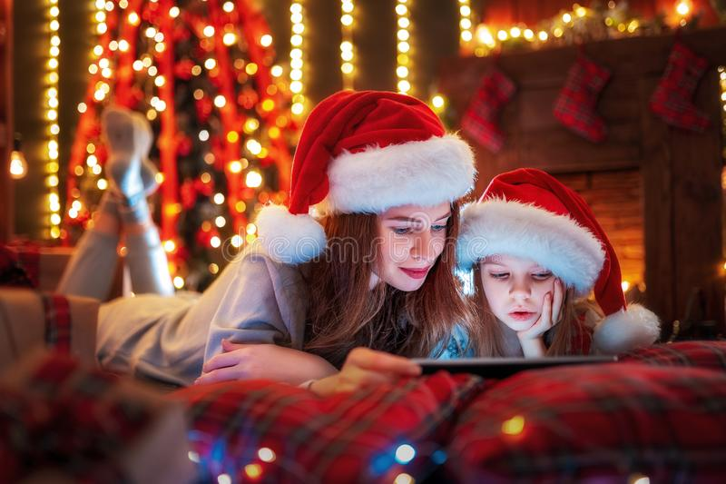 Smiling family mother and daughter in santas hats and pajamas watching funny video or choosing gifts on digital tablet royalty free stock image