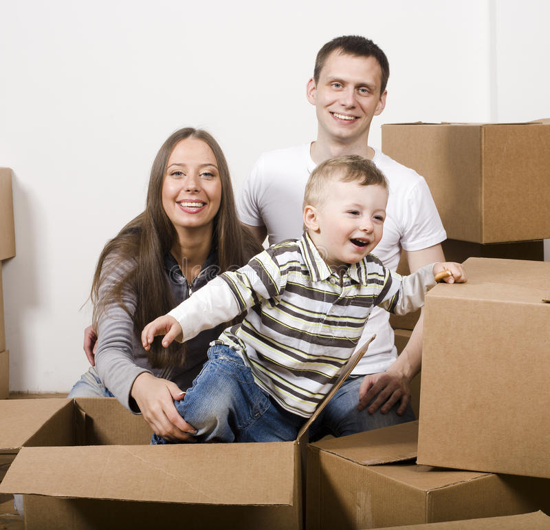 Smiling family in new house playing with boxes stock images