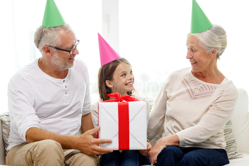 Smiling family in party hats with gift box at home. Family, generation, holidays and people concept - smiling grandfather, granddaughter and grandmother in party royalty free stock images