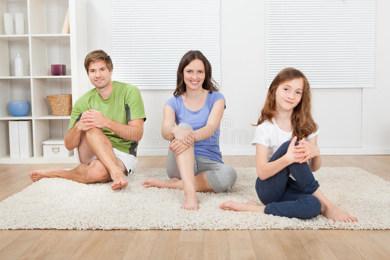 Smiling Family Performing Yoga On Rug royalty free stock images