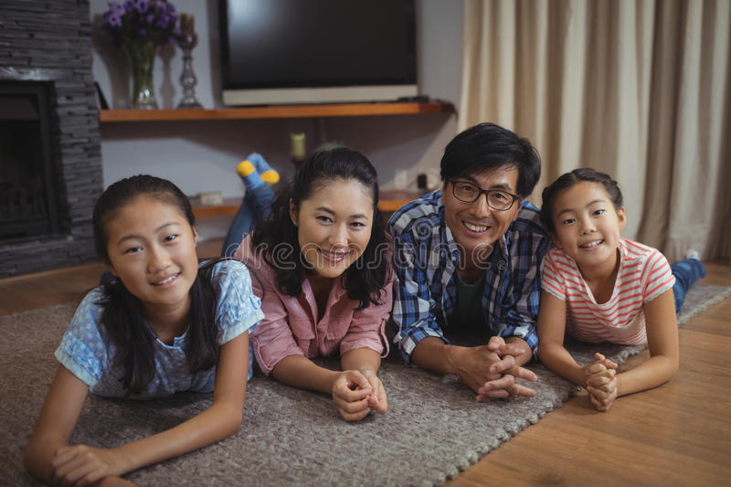 Smiling family relaxing on floor in living room stock photos
