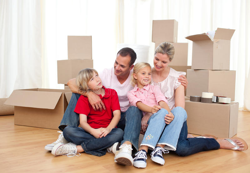 Smiling family relaxing while moving house royalty free stock photos