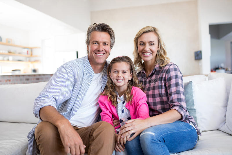Smiling family relaxing on sofa in living room stock images