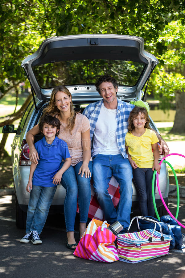 Smiling family sitting in the luggage space. Of a car royalty free stock photos