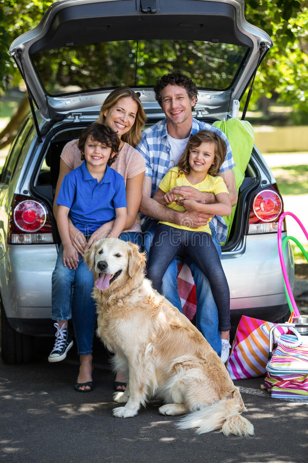 Smiling family sitting in the luggage space. Of a car stock image