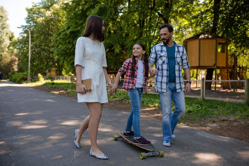Smiling family with a skateboard in summer park stock photography