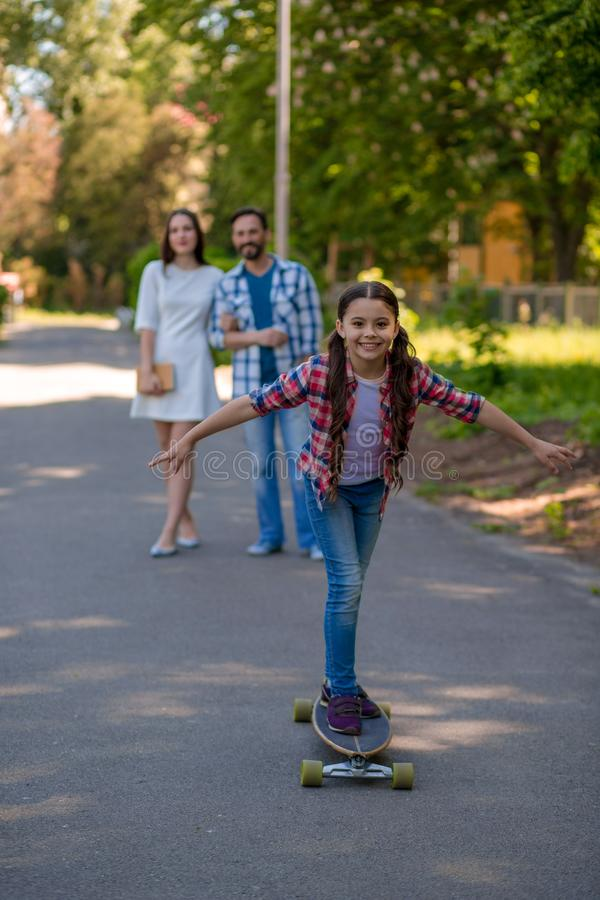 Smiling family with a skateboard in summer park royalty free stock image