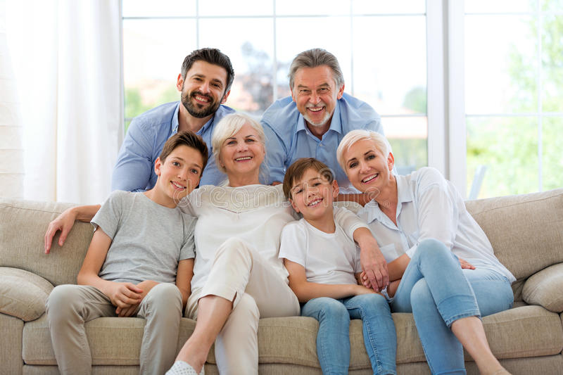 Smiling family on sofa. Family of three generations relaxing on sofa stock images