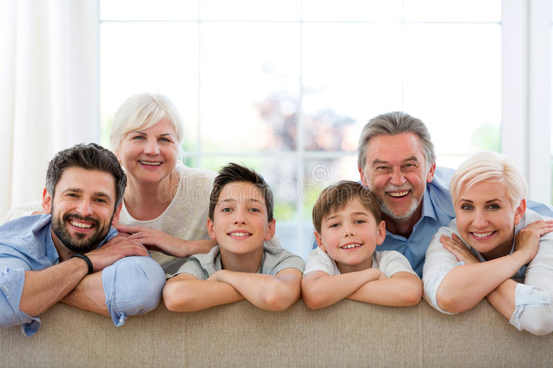 Smiling family on sofa. Family of three generations relaxing on sofa stock photos