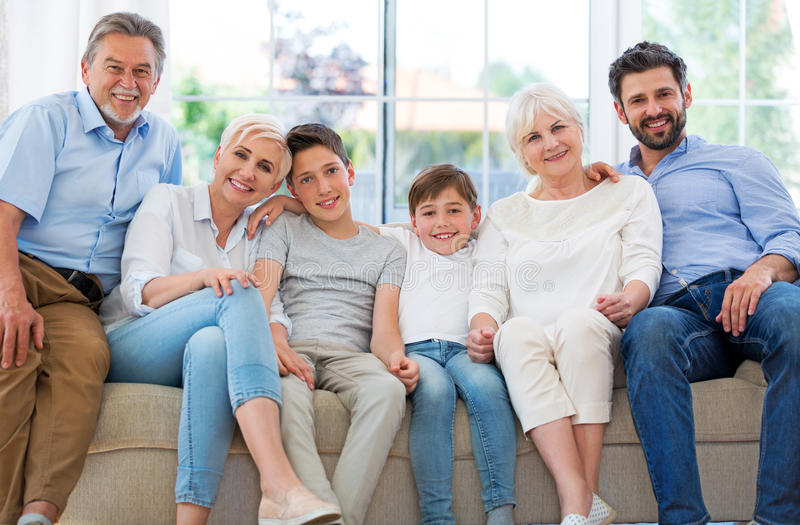 Smiling family on sofa. Family of three generations relaxing on sofa stock photography