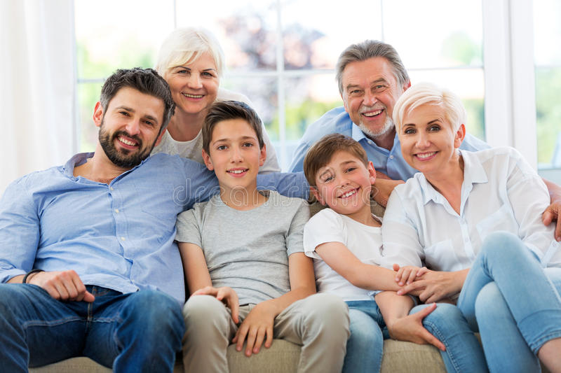 Smiling family on sofa. Family of three generations relaxing on sofa royalty free stock images