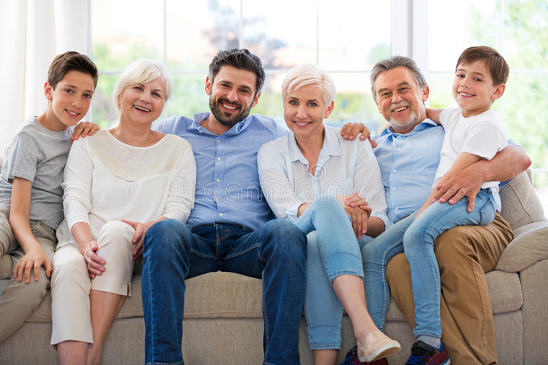 Smiling family on sofa. Family of three generations relaxing on sofa royalty free stock photography