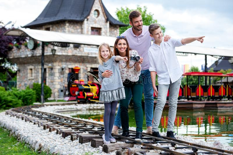 Smiling family standing on the railway of an amusement park royalty free stock images