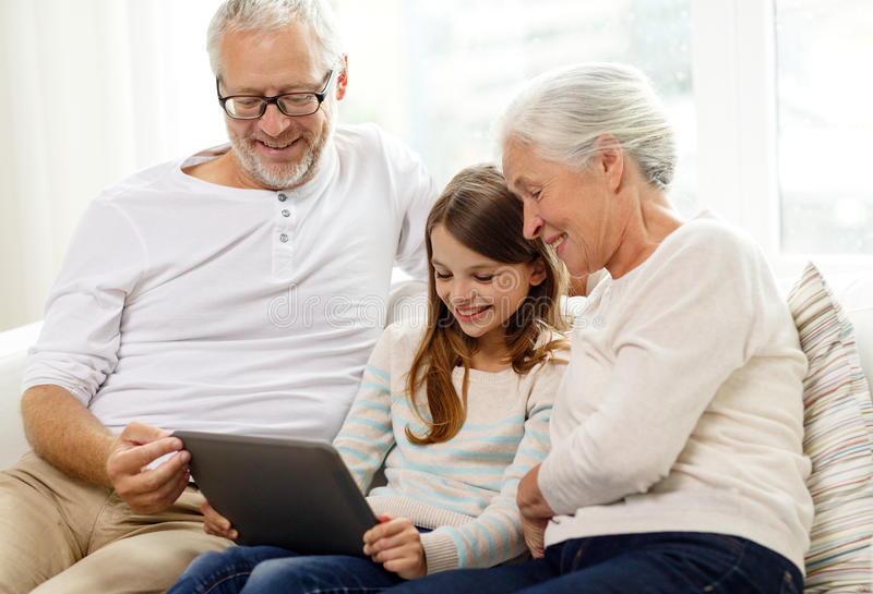 Smiling family with tablet pc at home stock photos