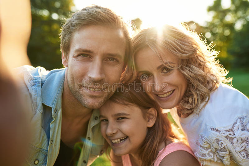 Smiling family taking a selfie together outside stock photography