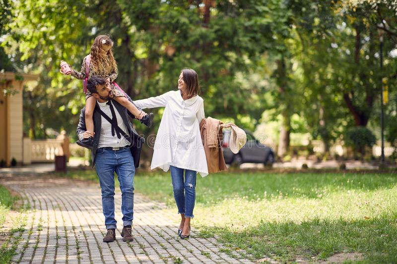 Smiling family walking from school with there schoolgirl royalty free stock photo