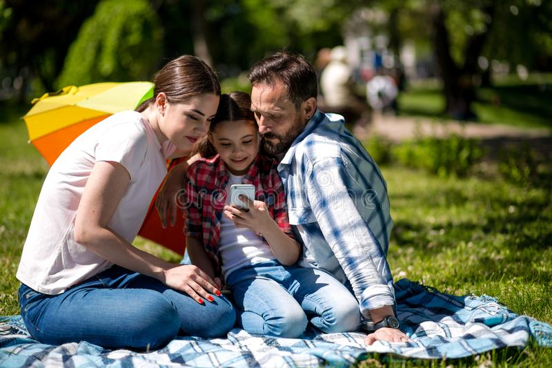 Smiling Family Watching Photo On Mobile Phone While Sitting On The Blanket In The Park. royalty free stock image