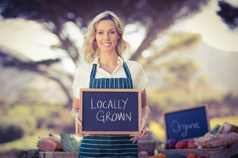 Smiling farmer woman holding a locally grown sign. Portrait of a farmer woman holding a locally grown sign stock photo
