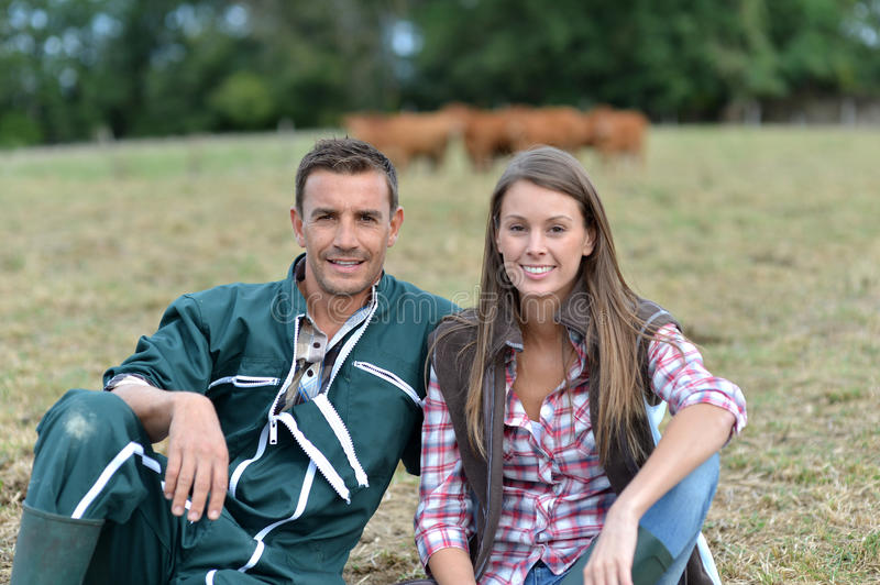 Smiling farmers. Couple of farmers sitting in field stock photos