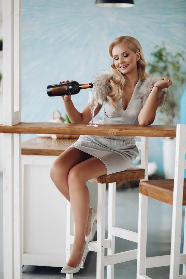 Smiling fashion beautiful woman pouring champagne from bottle into glass sitting on bar counter stock photography
