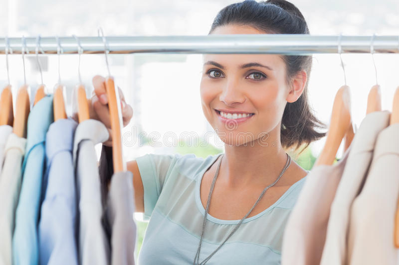 Download Smiling Fashion Designer Looking At Clothes Stock Photo - Image: 31801320