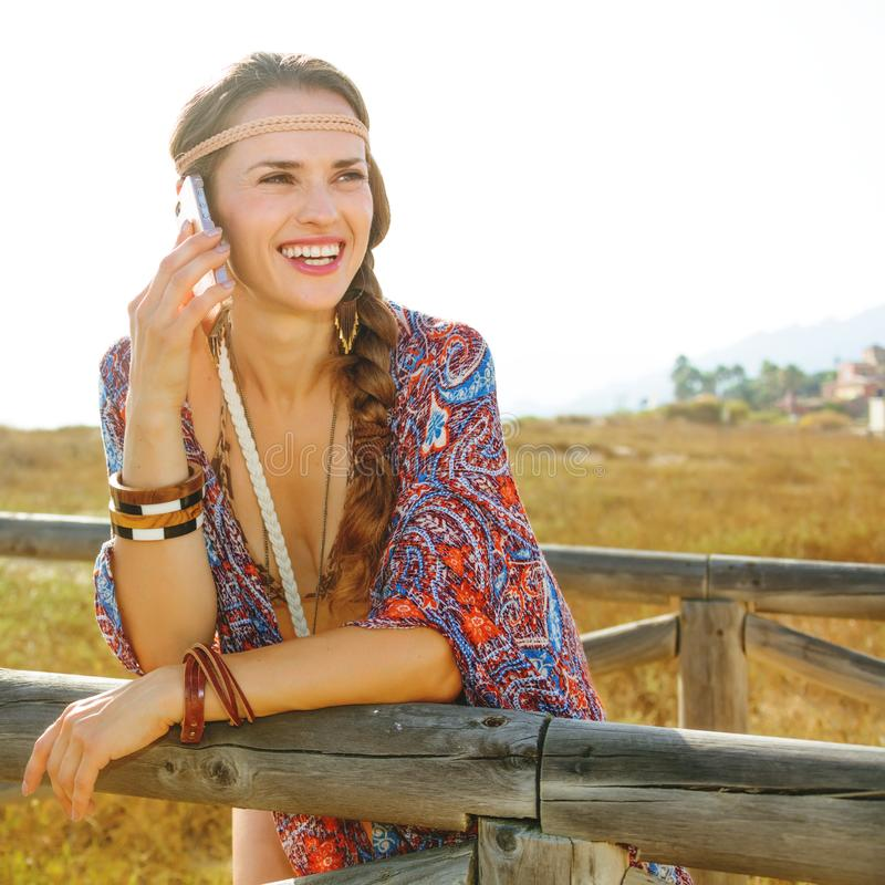 Smiling fashion gypsy style girl outdoors talking on cell phone royalty free stock photography