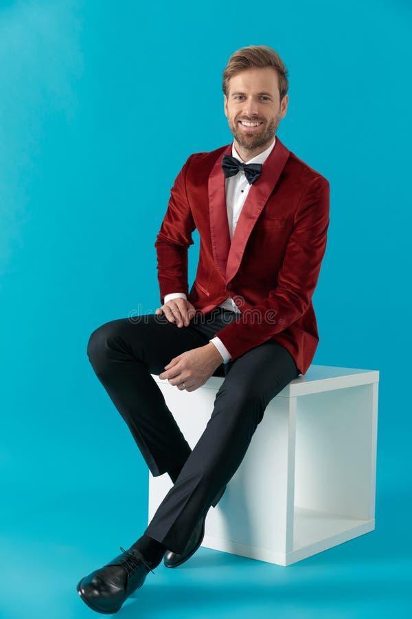 Smiling fashion model sitting and wearing red velvet tuxedo stock photo