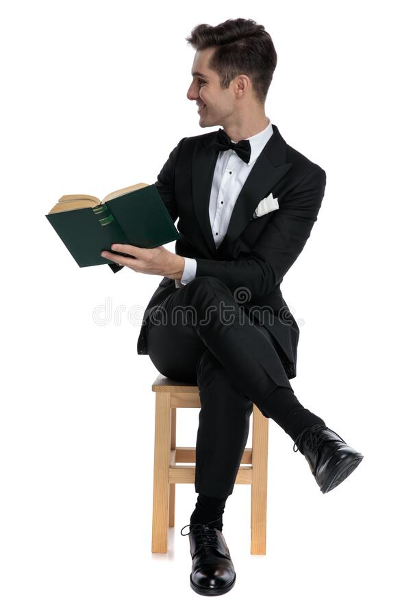 Smiling fashion model holding book and looking to side stock photos