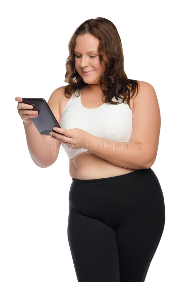 Smiling fat athletic woman with tablet royalty free stock photo