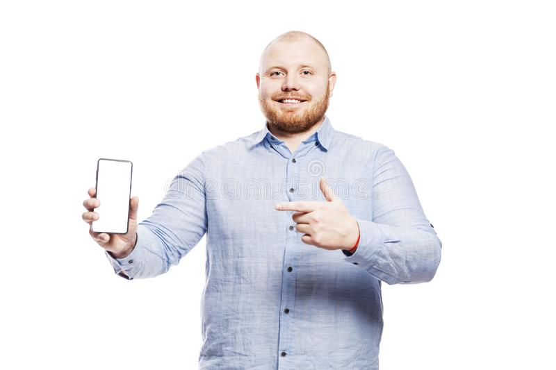 Smiling fat red-haired young man with a beard in a blue shirt with a phone in his hand. Shows a finger on an isolated screen. stock photo
