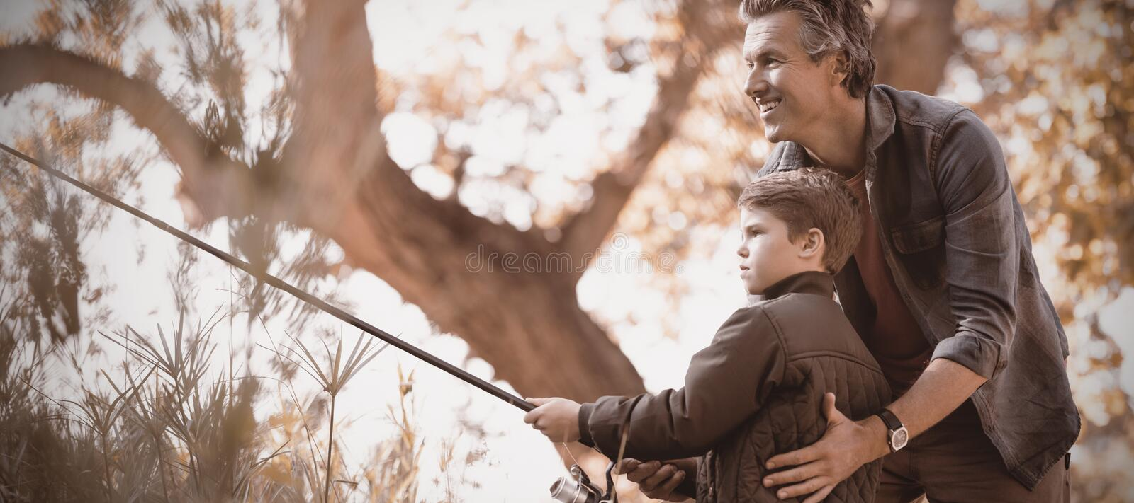Smiling father assisting son while fishing in forest. Smiling father assisting son while fishing on sunny day in forest stock photography