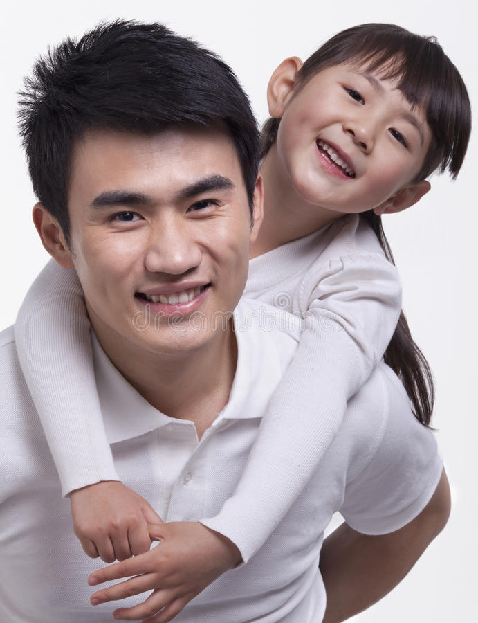 Smiling father carrying daughter on his back, studio shot royalty free stock image