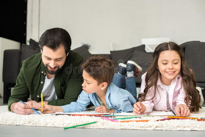 Smiling father with cute kids lying on carpet and drawing with colored. Pencils stock photo