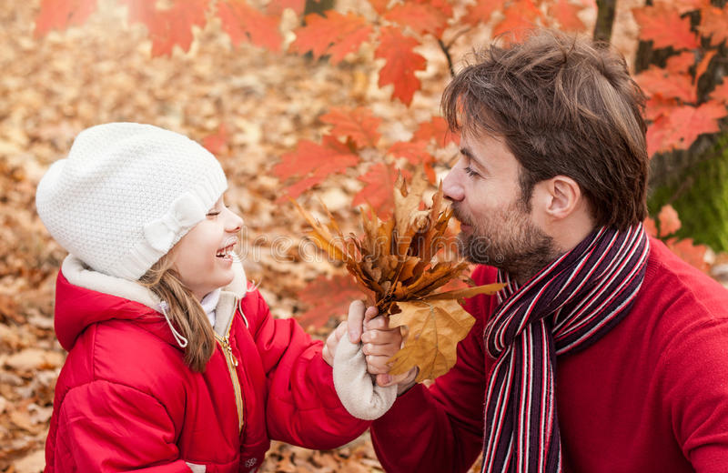 Smiling father and daughter having fun outdoor in an autumn park. Smiling, cheerful father and daughter having fun outdoor in the park during autumn - close up royalty free stock images