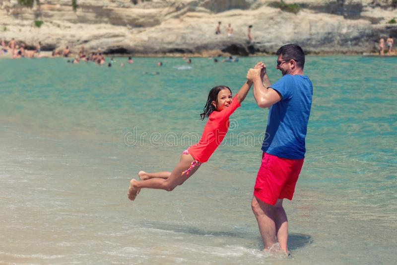 Smiling father and daughter playing together on beach, happy dad and cute little girl playing at seaside stock images