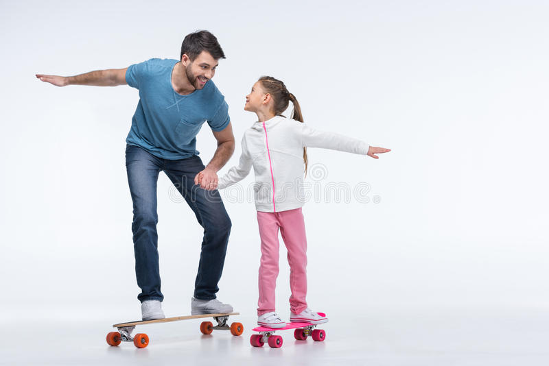 Smiling father and daughter riding skateboards. On white stock image