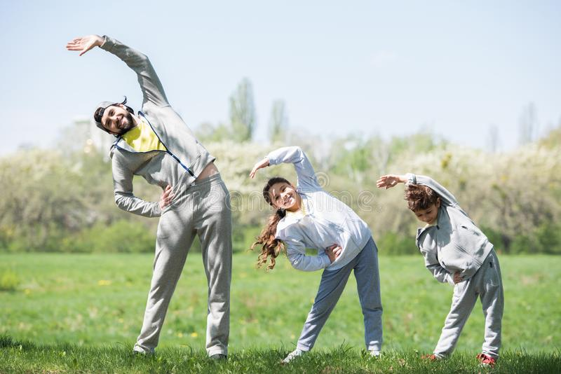 smiling father with daughter and son doing physical exercise on grassy meadow royalty free stock photos